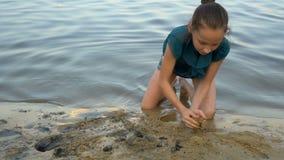 Un niño, chica joven, construye un castillo de la arena en el banco del río en la puesta del sol Ella se sienta en el borde y el  almacen de video