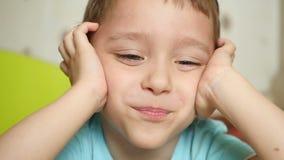 Un niño con alegría y una sonrisa mira la cámara, llevando a cabo sus manos detrás de su cabeza, cerrándose los oídos, primer almacen de metraje de vídeo