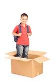 Un niño con el morral que se coloca en un cardbox Imagen de archivo