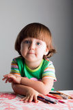 Un niño con los creyones y las etiquetas de plástico fotos de archivo libres de regalías