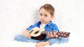 Un ni?o con placer toca una guitarra ac?stica canta una canci?n que se sienta en un sof? blanco almacen de metraje de vídeo