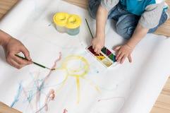 Un niño con un adulto aprende pintar el sol con las acuarelas Foto de archivo