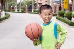 Un niño con un baloncesto Fotos de archivo
