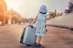 Un niño con un escape de la maleta de la casa Fotografía de archivo