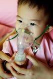 Un niño con una máscara y las manos de la madre Foto de archivo libre de regalías