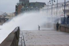 Un niño consigue empapado por una onda enorme en Porthcawl, el Sur de Gales, Reino Unido Imagen de archivo libre de regalías