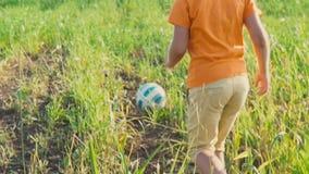 Un niño corre y bate la bola, futbolista joven El muchacho de 5 años golpea un balón de fútbol con el pie con sus pies en el alto almacen de metraje de vídeo