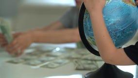 Un niño cuenta el dinero dólar para el viaje almacen de metraje de vídeo