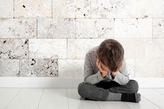 Un niño cuya depresión se está sentando en el piso fotos de archivo