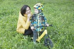 Un niño da las flores a su madre, para un paseo, un muchacho en una bicicleta Imagen de archivo