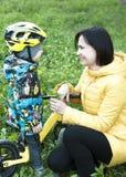 Un niño da las flores a su madre, para un paseo, un muchacho en una bicicleta Imágenes de archivo libres de regalías