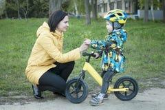 Un niño da las flores a su madre, para un paseo, un muchacho en una bicicleta Imagen de archivo libre de regalías