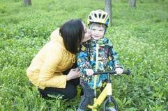 Un niño da las flores a su madre, para un paseo, un muchacho en una bicicleta Fotos de archivo