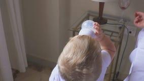 Un niño de un año bebe la leche, y su madre bebe el vino El concepto de una familia y de un alcoholismo disfuncionales metrajes