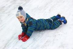 Un niño de cuatro años, muchacho, monta su estómago de una colina y de risas imagenes de archivo