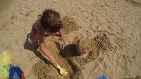 Un niño de la muchacha es el jugar feliz en la playa 2 FDV almacen de metraje de vídeo