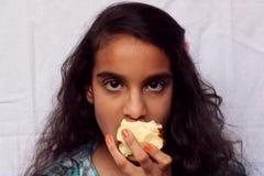 Un niño de la muchacha que come la manzana imagen de archivo