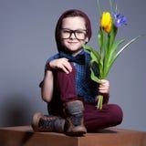 Un niño de ojos azules con los vidrios Un muchacho se sienta con una sonrisa en cara Imagen de archivo