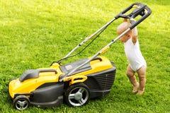 Un niño del año que muele la hierba con un grassmower foto de archivo libre de regalías