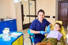 Un niño del muchacho y un hombre del dentista en la oficina del ` s del dentista Imagen de archivo