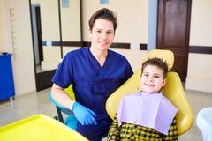 Un niño del muchacho y un hombre del dentista en la oficina del ` s del dentista Fotos de archivo libres de regalías