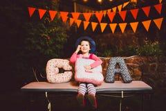 Un niño divertido que la muchacha se sienta en un banco en una decoración adornada festiva de la yarda con las guirnaldas brillan Fotos de archivo