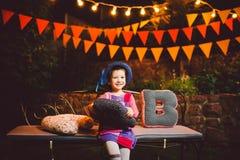 Un niño divertido que la muchacha se sienta en un banco en una decoración adornada festiva de la yarda con las guirnaldas brillan Imagen de archivo