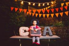 Un niño divertido que la muchacha se sienta en un banco en una decoración adornada festiva de la yarda con las guirnaldas brillan Foto de archivo libre de regalías