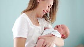 Un niño dos-semana-viejo sonríe en un sueño, mintiendo en los brazos del ` s de la madre Alegría de la maternidad un nuevo miembr almacen de metraje de vídeo