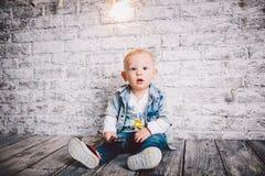 Un niño elegante, muchacho, de un año, se sienta en un piso de madera y en un fondo de la pared de ladrillo Lo visten en una chaq foto de archivo