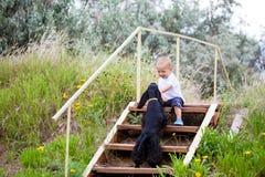 Un niño en el jardín con el perro Imagen de archivo