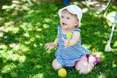 Un niño en la camisa rayada se está sentando en la hierba Imagen de archivo libre de regalías