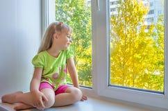 Un niño en la ventana. foto de archivo