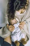 Un niño en los brazos de su madre Él oculta su cara con sus manos Foto de archivo