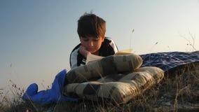 Un niño en una comida campestre que lee un libro en la puesta del sol metrajes