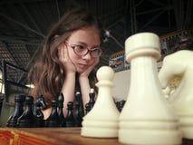 Un niño en vidrios juega a un juego del ajedrez fotografía de archivo
