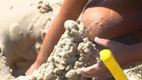 Un niño está construyendo un castillo en la playa almacen de metraje de vídeo