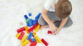Un niño está jugando con los bloques del color en un fondo blanco Visión desde arriba El concepto de desarrollo infantil almacen de metraje de vídeo