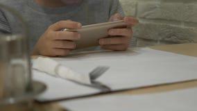 Un niño está jugando con un teléfono móvil en la tabla, esperando una orden en un café muchacho que se sienta en la tabla, sosten metrajes