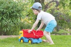 Un niño está jugando en la hierba con un coche rojo grande del juguete Imagenes de archivo