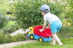 Un niño está jugando en la hierba con un coche rojo grande del juguete Imágenes de archivo libres de regalías