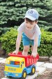 Un niño está jugando en la hierba con un coche rojo grande del juguete Fotografía de archivo