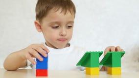 Un niño está jugando en los bloques del color, sentándose en una tabla en un fondo blanco, en la cámara lenta metrajes