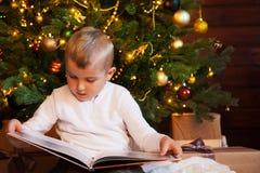Un niño está leyendo un libro que se sienta por el árbol de navidad Vagos oscuros Foto de archivo