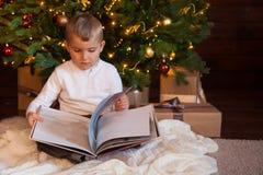 Un niño está leyendo un libro que se sienta por el árbol de navidad Vagos oscuros Imagen de archivo libre de regalías