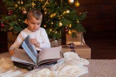 Un niño está leyendo un libro que se sienta por el árbol de navidad Vagos oscuros Imágenes de archivo libres de regalías