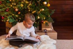 Un niño está leyendo un libro que se sienta por el árbol de navidad Vagos oscuros Foto de archivo libre de regalías