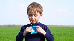 Un niño feliz bebe el jugo de una caja de cartón de un fabricante desconocido El muchacho bebe al aire libre r almacen de metraje de vídeo