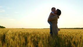 Un niño feliz corre en los brazos de su madre sobre un campo de trigo, después de lo cual la madre abraza y besa al niño metrajes