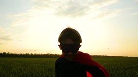 Un niño feliz en un traje del super héroe corre a través de la hierba verde hacia la cámara en un fondo de la puesta del sol almacen de metraje de vídeo